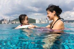 Asiatische chinesische Mutter und daugther, die am Swimmingpool spielt Lizenzfreie Stockfotografie