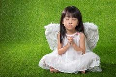 Asiatische chinesische tragende Engelsflügel des kleinen Mädchens und Beten Stockfoto