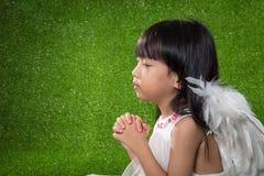 Asiatische chinesische tragende Engelsflügel des kleinen Mädchens und Beten Lizenzfreie Stockfotografie