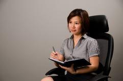 Asiatische Dame in der Geschäftskleidung, Holdingfeder lizenzfreie stockfotos