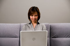 Asiatische Dame in der Geschäftskleidung, unter Verwendung eines Computers Stockfotos