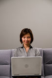 Asiatische Dame in der Geschäftskleidung, unter Verwendung eines Computers Lizenzfreie Stockfotografie