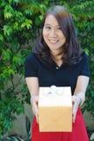 Asiatische Dame, die ein gelbes Geschenk lächelt und hält Stockbild