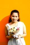 Asiatische Dame im Kleiderreihen-Griffblumenstrauß stockfoto