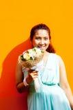 Asiatische Dame im Kleiderreihen-Griffblumenstrauß stockfotografie