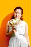 Asiatische Dame im Kleiderreihen-Griffblumenstrauß lizenzfreie stockfotografie