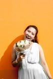 Asiatische Dame im Kleiderreihen-Griffblumenstrauß lizenzfreies stockfoto