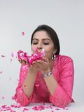 Asiatische Dame mit den rosafarbenen Blumenblättern in ihrer Palme Stockfoto