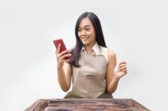 Asiatische Dame mit Kittelschürzeblick auf mobilen Schirm lizenzfreie stockfotos
