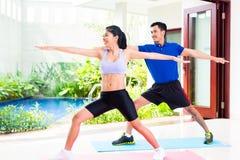 Asiatische Eignungspaare am Sporttraining im tropischen Haus Stockfotos