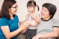 Asiatische Eltern, die kleiner Tochter eine Flasche mit Getränk geben Stockfoto