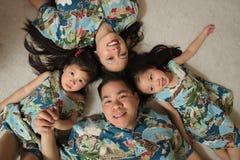 Asiatische Familie, die auf dem Bodenlächeln legt Lizenzfreie Stockbilder