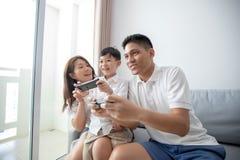 Asiatische Familie, die den Spaß zusammen spielt Operatorkonsolespiele hat, lizenzfreies stockbild