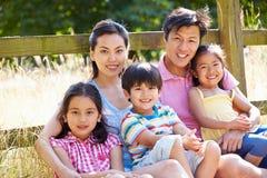 Asiatische Familie, die durch Tor auf Weg in der Landschaft sich entspannt stockfotografie