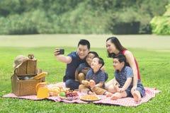 Asiatische Familie, die ein Foto im Park macht Stockbild