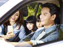 Asiatische Familie, die eine Autofahrt genießt Lizenzfreies Stockbild