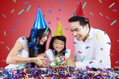 Asiatische Familie, die einen Geburtstagskuchen schneidet stockbild