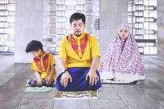 Asiatische Familie, die Salat in der Moschee tut Stockfoto