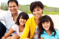 Asiatische Familie, die am Strand lacht und spielt Stockbilder
