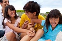 Asiatische Familie, die am Strand lacht und spielt Lizenzfreies Stockfoto