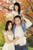Asiatische Familie, die unter Herbstbaum steht Lizenzfreies Stockbild