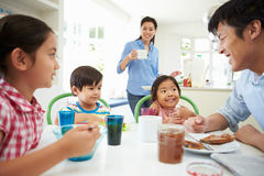 Asiatische Familie, die zusammen in der Küche frühstückt Stockfotografie