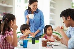 Asiatische Familie, die zusammen in der Küche frühstückt Stockbilder