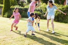 Asiatische Familie, die zusammen im Sommer-Garten spielt Lizenzfreies Stockfoto