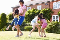 Asiatische Familie, die zusammen im Sommer-Garten spielt stockfotos