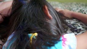 Asiatische Familie mit der Mutter, die das Haar ihrer Tochter gegen L?use behandelt stock video