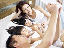 Asiatische Familie mit zwei Kindern, die digitale Tablette im Bett verwenden Lizenzfreie Stockfotos