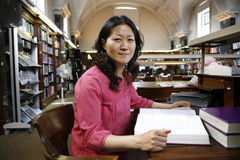 Asiatische Frau in der Bibliothek Stockbilder