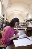 Asiatische Frau in der Bibliothek lizenzfreie stockfotos