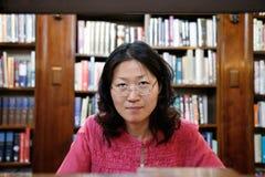 Asiatische Frau in der Bibliothek stockbild