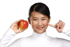 Asiatische Frau der Junge recht, die einen Apfel isst Lizenzfreie Stockfotografie