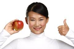 Asiatische Frau der Junge recht, die einen Apfel isst Lizenzfreies Stockbild
