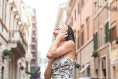 Asiatische Frau der Junge recht, die unter Verwendung der städtischen Straße des Handys lächelt Stockfoto