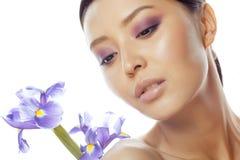 Asiatische Frau der Junge recht mit purpurrotem Orchideenabschluß der Blume oben auf weißem Hintergrundbadekurort, Gesundheitswes Stockfoto