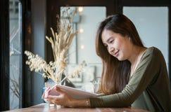 Asiatische Frau der Nahaufnahme, die ein Buch am hölzernen Gegenschreibtisch in der Kaffeestube mit Lächelngesicht in der glückli lizenzfreie stockbilder