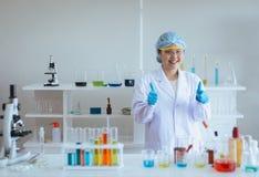 Asiatische Frau des glücklichen Wissenschaftlers, die medizinische Chemikalien studiert und Daumen oben im Labor zeigt stockfotografie