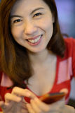 Asiatische Frau des Lächelns haben Spaß mit Handy Stockbilder