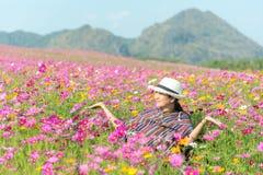 Asiatische Frau des Reisenden entspannen sich und Freiheit im schönen blühenden Kosmosblumengarten lizenzfreies stockfoto