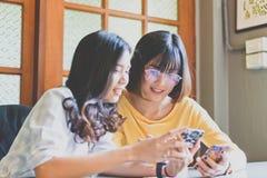 Asiatische Frau des schönen Studenten, die intelligentes Telefon verwendet und Bericht Arbeits Stockbild