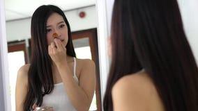 Asiatische Frau des Schönheitsporträts, die zuhause Make-up mit Bürste des Backenblickes am Spiegel anwendet stock video footage