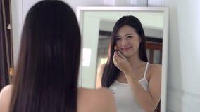 Asiatische Frau des Schönheitsporträts, die zuhause Make-up mit Bürste des Backenblickes am Spiegel anwendet stock footage