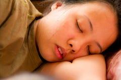 Asiatische Frau, die auf Bett schläft Stockbild