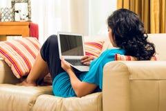 Asiatische Frau, die auf Couch sitzt Stockfotografie