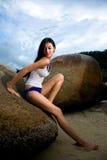 Asiatische Frau, die auf dem Felsen sich entspannt Lizenzfreie Stockfotografie