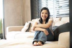 Asiatische Frau, die auf dem Sofa mit Kissen sitzt Stockfotografie