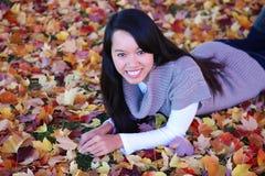 Asiatische Frau, die in Blätter legt Stockfoto